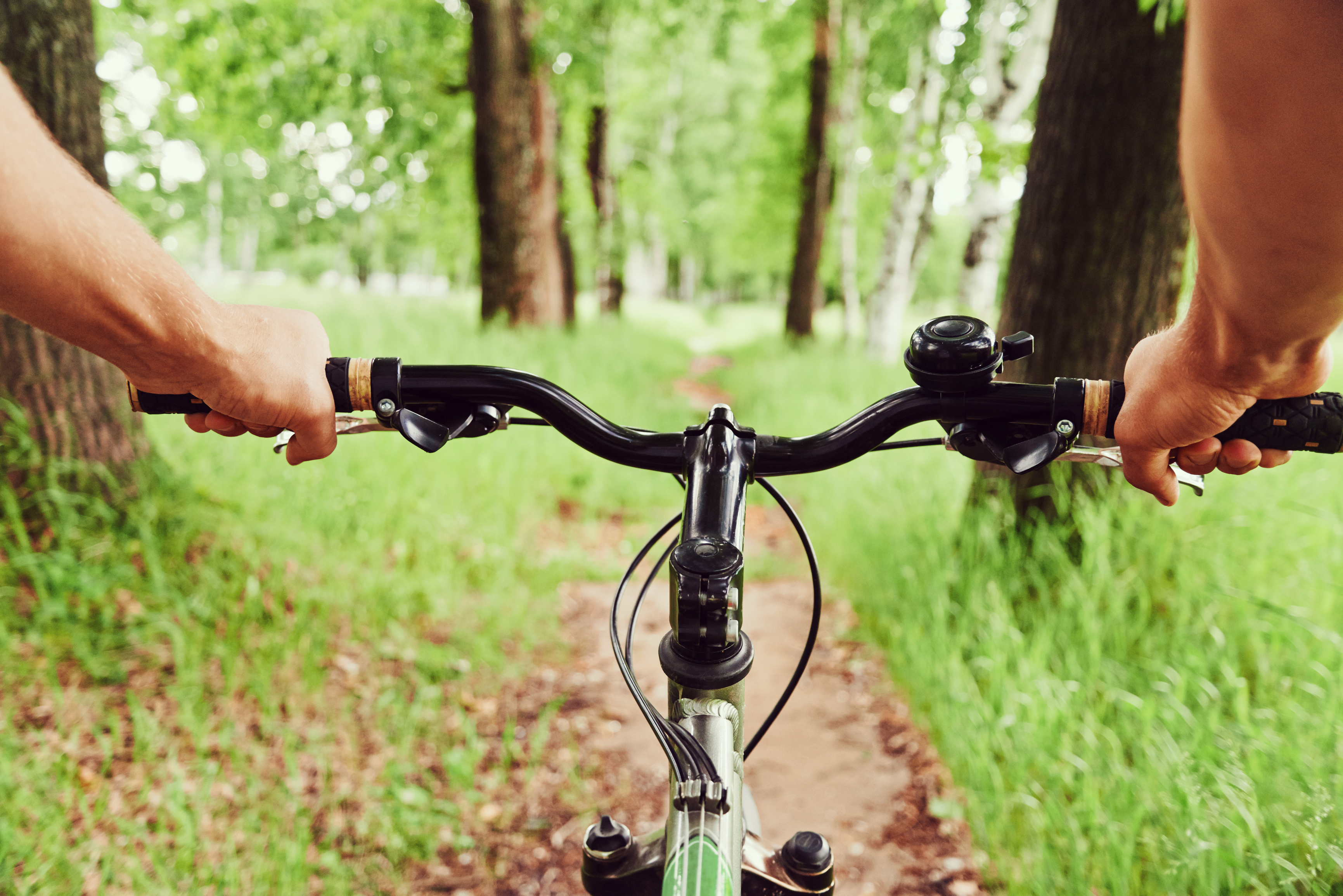 Close-up image of cyclist man hands on handlebar riding mountain bike on trail in summer park, face is not visible